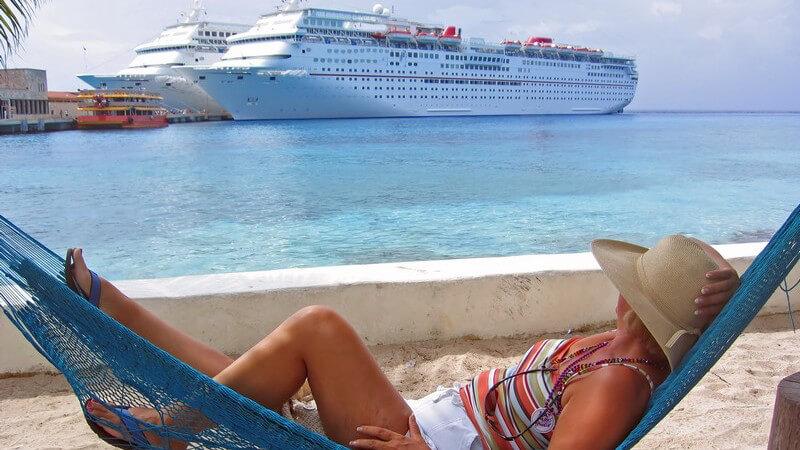 Frau mit Strohhut liegt in blauer Hängematte, blickt auf Kreuzfahrtschiffe