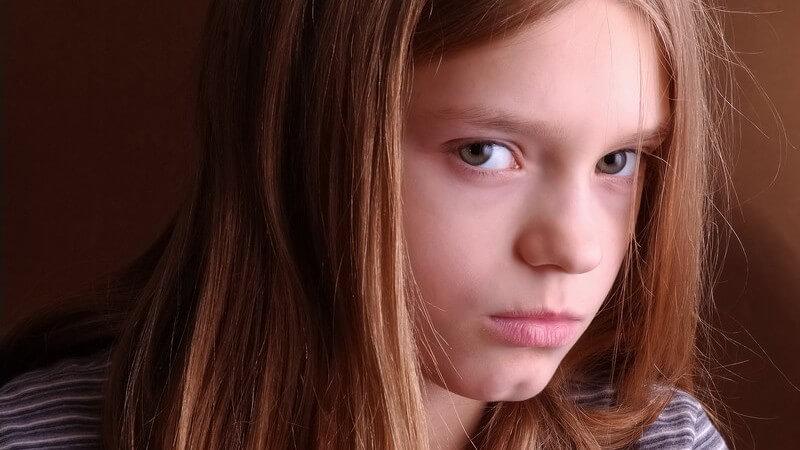 Rothaariges Mädchen blickt verärgert in die Kamera