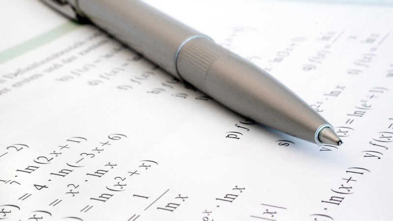 Silberner Kugelschreiber auf einem Buch mit mathematischen Formeln