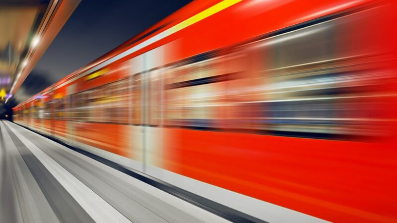 S-Bahn oder Zug fährt nachts durch einen beleuchteten Bahnhof