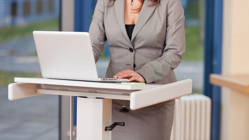 Frau in grauem Blazer und Rock arbeitet an einem Laptop an einem Stehpult