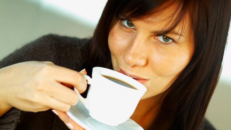 Junge brünette Frau schaut in Kamera und trinkt an Tasse Kaffee