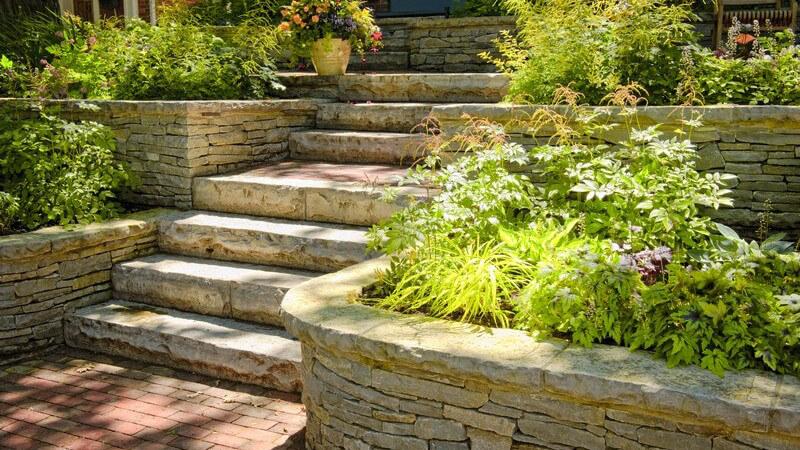 Garten mit Treppe, Mauern und Beeten aus Naturstein