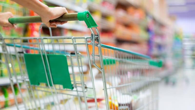 Einkaufswagen wird im Gang eines Supermarkts geschoben, im Hintergrund Regale mit Lebensmitteln