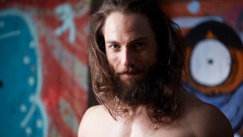 Portrait eines Mannes mit langen Haaren, Vollbart und nacktem Oberkörper vor Graffiti-Hintergrund