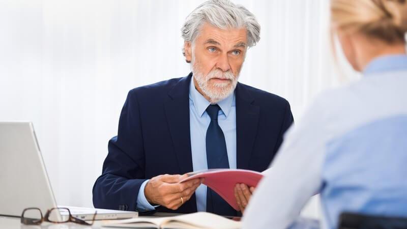 Älterer Chef mit grauen Haaren und Vollbart sitzt einer blonden Bewerberin gegenüber und betrachtet die Bewerbungsmappe