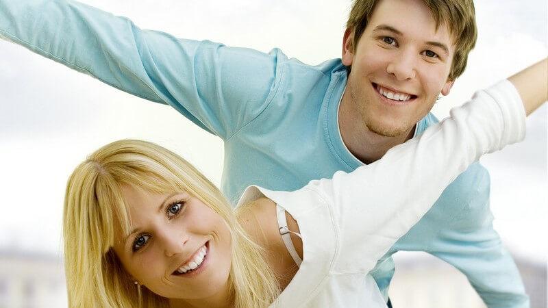 Junges Paar mit ausgestreckten Armen, er hinter ihr und über sie gebeugt