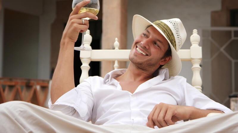 Junger hellgekleideter Mann mit weißem Hut und Glas Wein auf Schaukelstuhl vor Villa