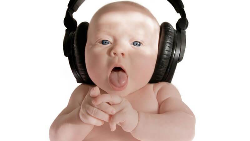 Baby mit offenem Mund trägt riesige Kopfhörer, weißer Hintergrund