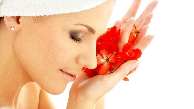 Junge Frau mit Handtuch am Kopf im Wasser, hält rote Blüten vors Gesicht