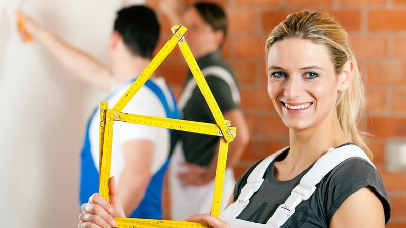 Frau hält Zollstock in Form eines Hauses, hinter ihr zwei Handwerker: Renovierung