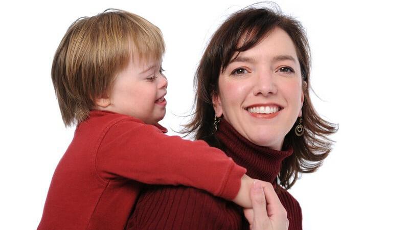 Lächelnde Mutter trägt lächelndes, behindertes Kind mit Down-Syndrom auf dem Rücken Huckepack