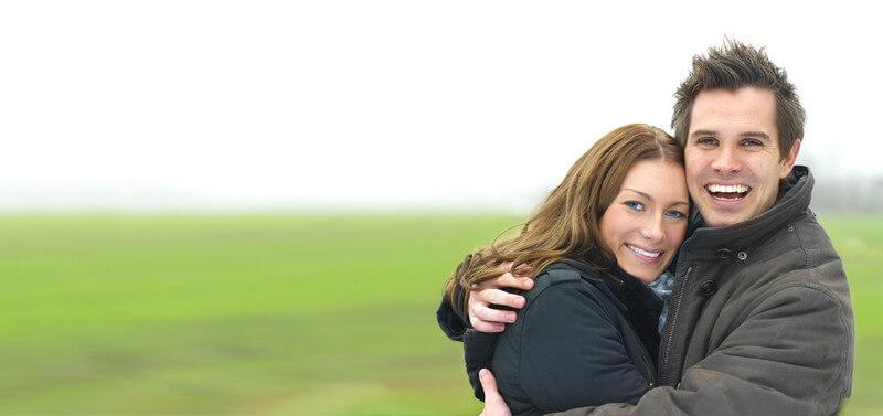 Junges Paar in Jacken umarmen sich, lächeln in die Kamera, hinten grüne Wiese
