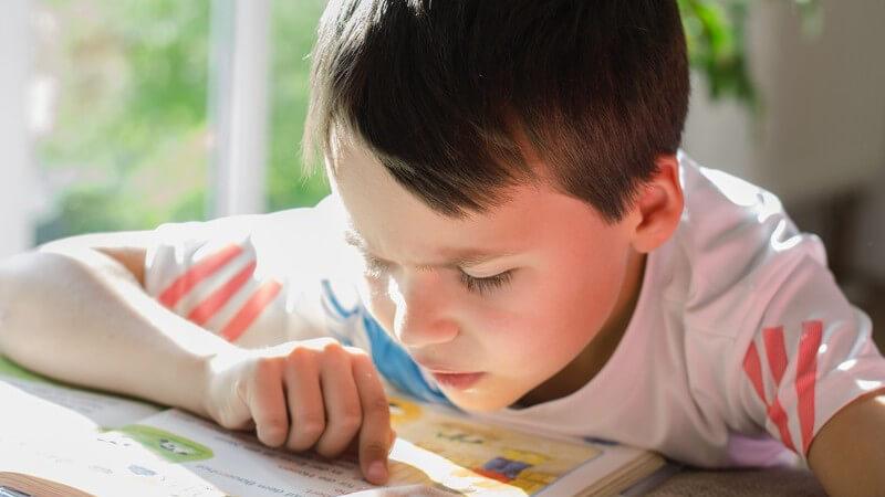 Kleiner Junge beim Lesen in einem Buch