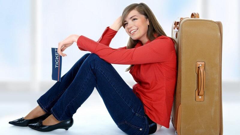 Junge Frau sitzt am Koffer angelehnt und hält Ticket in Hand