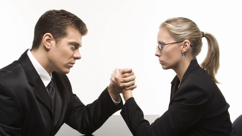 Mann und Frau im Businessoutfit schauen sich kalt an und machen Armdrücken