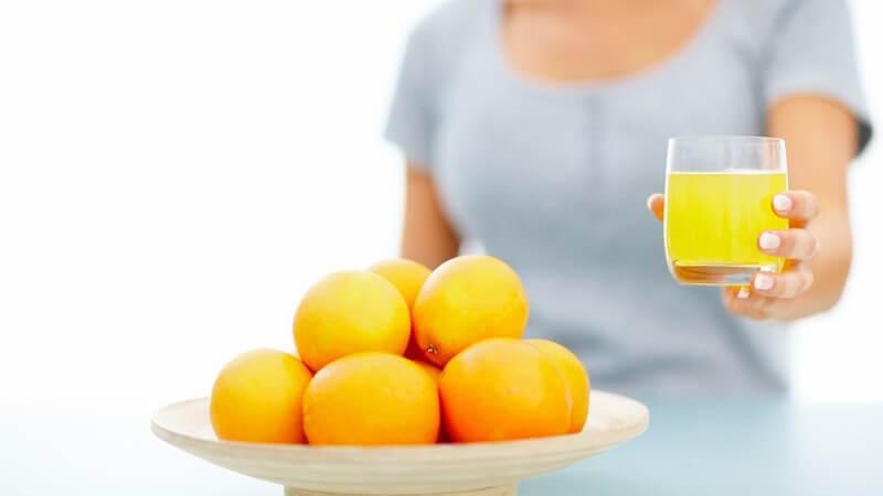 Teller mit frischen Orangen, im Hintergrund hält Frau Glas mit Orangensaft in die Kamera