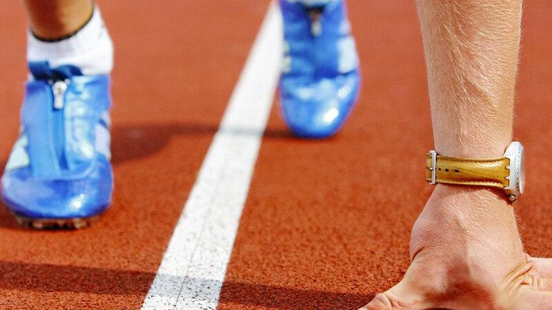 Sprinter mit blauen Laufschuhen und goldener Uhr in Startposition