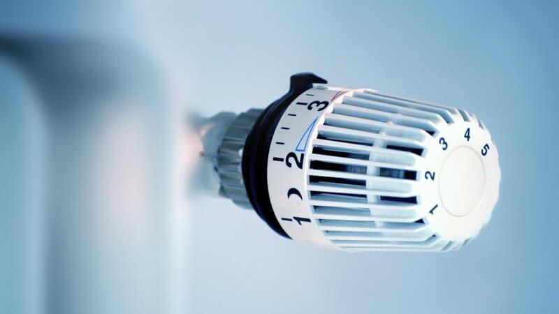 Nahaufnahme Thermostat einer Heizung, mittlere Wärmestufe, grauer Hintergrund