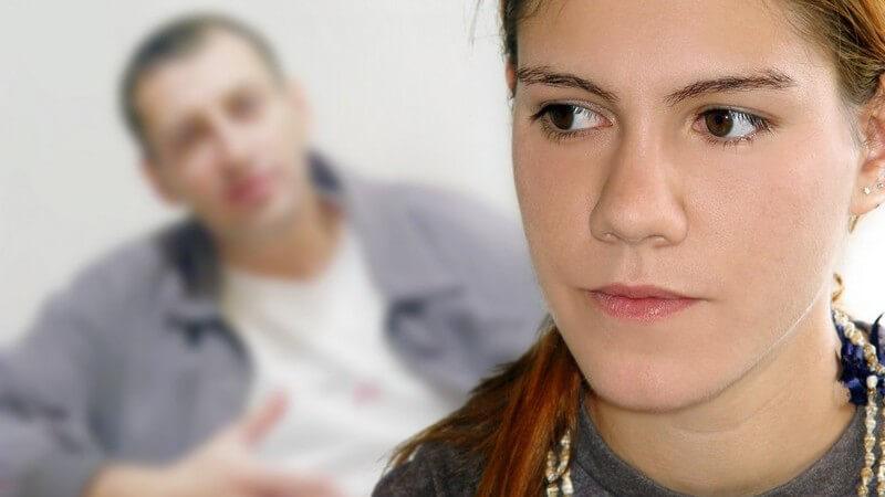 Jugendliche schaut enttäuscht und wütend zur Seite, im Hintergrund ihr verständnisloser Freund