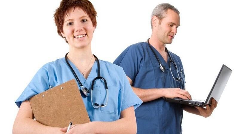 Junge Frau mit blauem Arzt-Hemd, Krankenakte und Stetoskop vorne, hinten grauhaariger Arzt, Stetoskop, mit Laptop