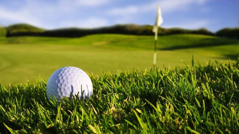 Nahaufnahme Golfball auf grüner Wiese, im Hintergrund Golffahne und blauer Himmel