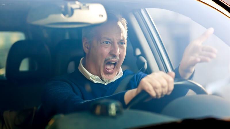 Wütender Mann am Steuer seines Autos schreit