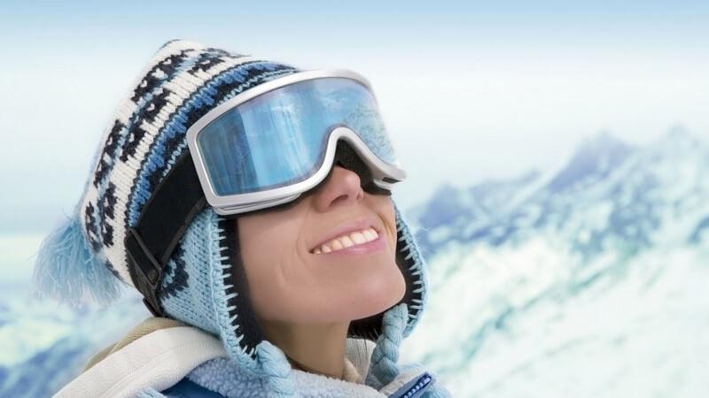 Junge Frau mit Strickmütze und Skibrille, dahinter Berg Panorama