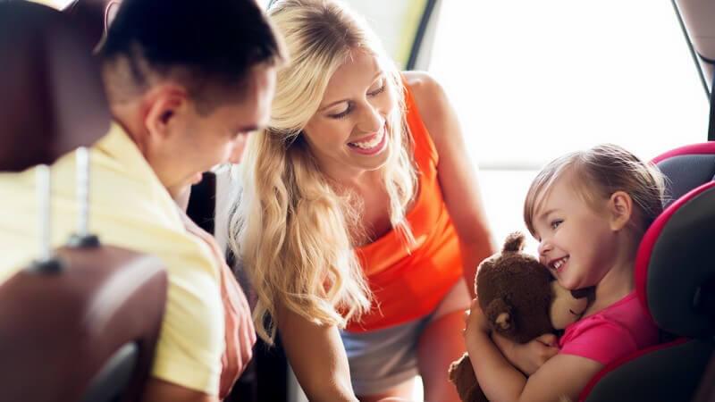 Fröhliche Mutter schnallt ihre Tochter mit Teddy im Kindersitz an, der Vater beugt sich im Auto nach hinten