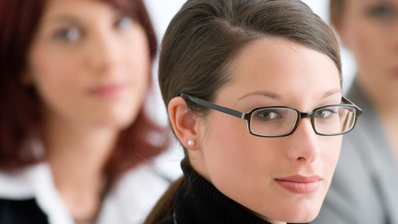 Brünette Frau mit strenger Brille, Rollkragen und zurückgebundenem Haar, dahinter rothaarige Frau in Bluse