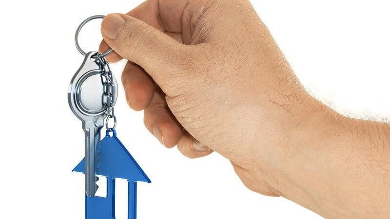 Männliche Hand hält Schlüssel mit Haus-Schlüsselanhänger hoch
