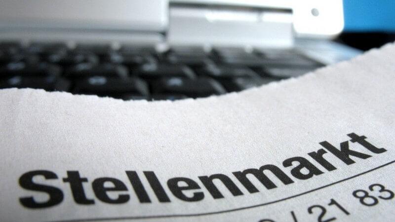 """Nahaufnahme Zeitungstitel """"Stellenmarkt"""" vor einem Computer oder Laptop zur Arbeitssuche"""
