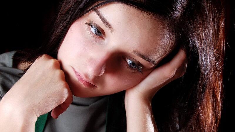 Mädchen mit langen, dunklen Haaren, den Kopf seitlich in die Hand gelehnt, schaut traurig nach unten