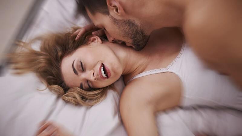 Paar beim Sex auf dem Bett, er liebkost ihren Hals, sie liegt mit geschlossenen Augen unten, trägt ein Unterhemd
