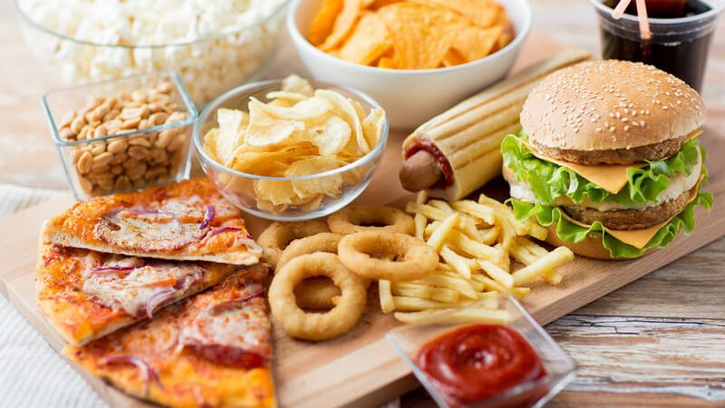 Diverse Fast Food-Speisen auf Holzbrett - Pizza, Burger, Pommes, Chips und Cola