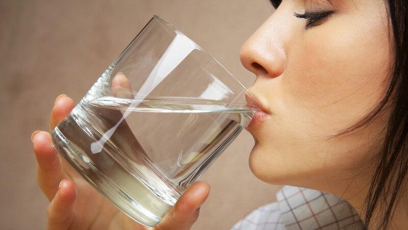 Junge Frau trinkt am Glas mit Wasser