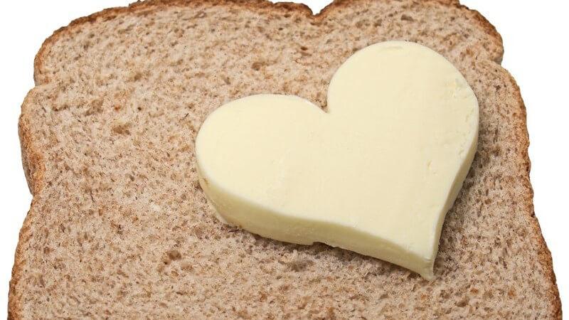 Stück Butter in Herzform auf Scheibe Toast, weißer Hintergrund