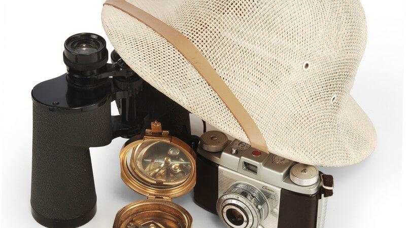 Safarihut, Kompass, Fernglas, Fotoapparat auf weißem Hintergrund