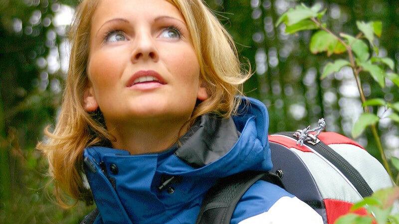 Frau mit Jacke und Rucksack im Wald beim Wandern