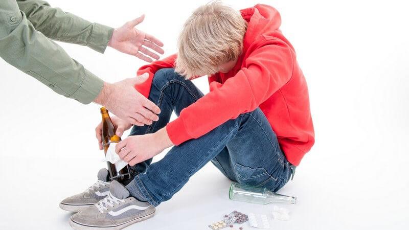 Jugendlicher in rotem Kapuzenpullover sitzt mit Bierflasche neben Tabletten, ein Erwachsener reicht ihm die Hände