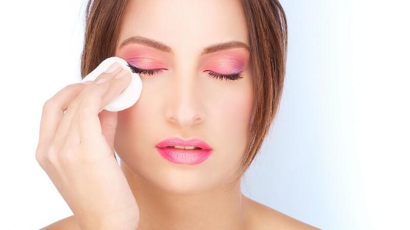 Geschminkte Frau streicht sich mit Wattepad über Auge