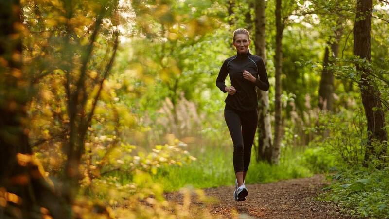 Junge Frau im Sportoutfit joggt durch den Wald