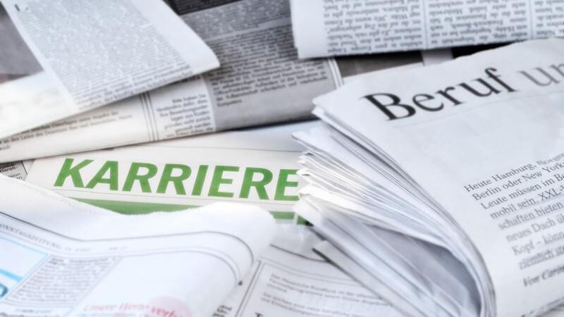 Gefaltete Zeitungen mit den Bereichen Beruf und Karriere für die Arbeitssuche