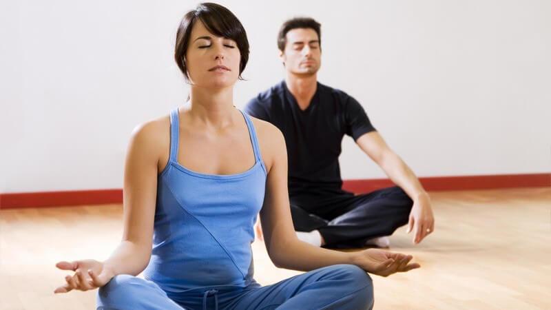 Holzboden, Frau in blauer Sportkleidung vorne, Mann mit schwarzer Sportkleidung hinten, Schneidersitz, Meditation