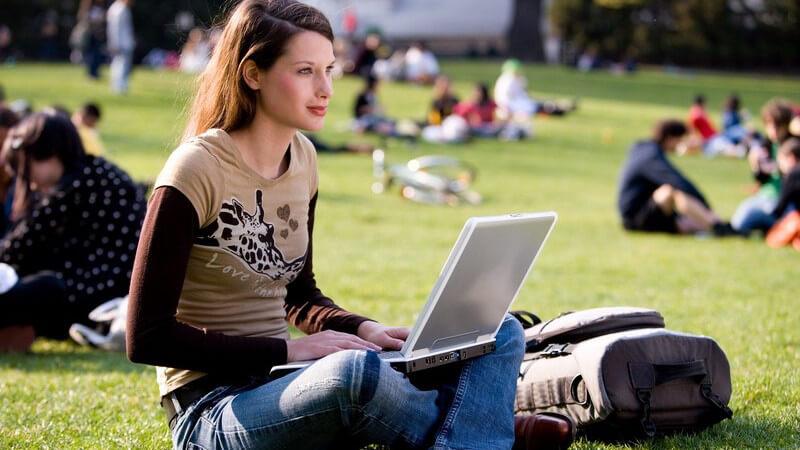 Schlanke Frau im Schneidersitz mit Laptop im Park
