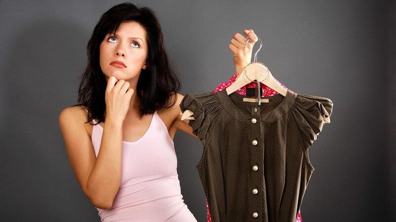 Junge Frau hält zwei Kleider in Hand und überlegt, welches sie nehmen soll