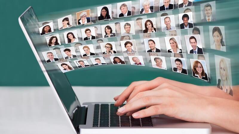 Hände auf Latopt oder Notebook Tastatur, davor Bewerbungsbilder von Geschäftsleuten