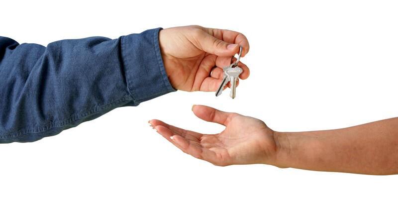 Zwei Arme, eine Hand reicht der anderen einen Schlüsselbund
