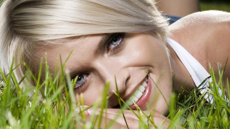 Nahaufnahme Gesicht einer jungen Frau, die auf einer Wiese liegt