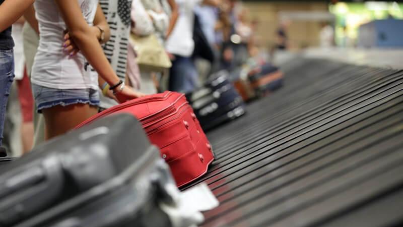 Gepäckausgabeband am Flughafen: Fluggäste warten an der Gepäckförderanlage auf ihre Koffer